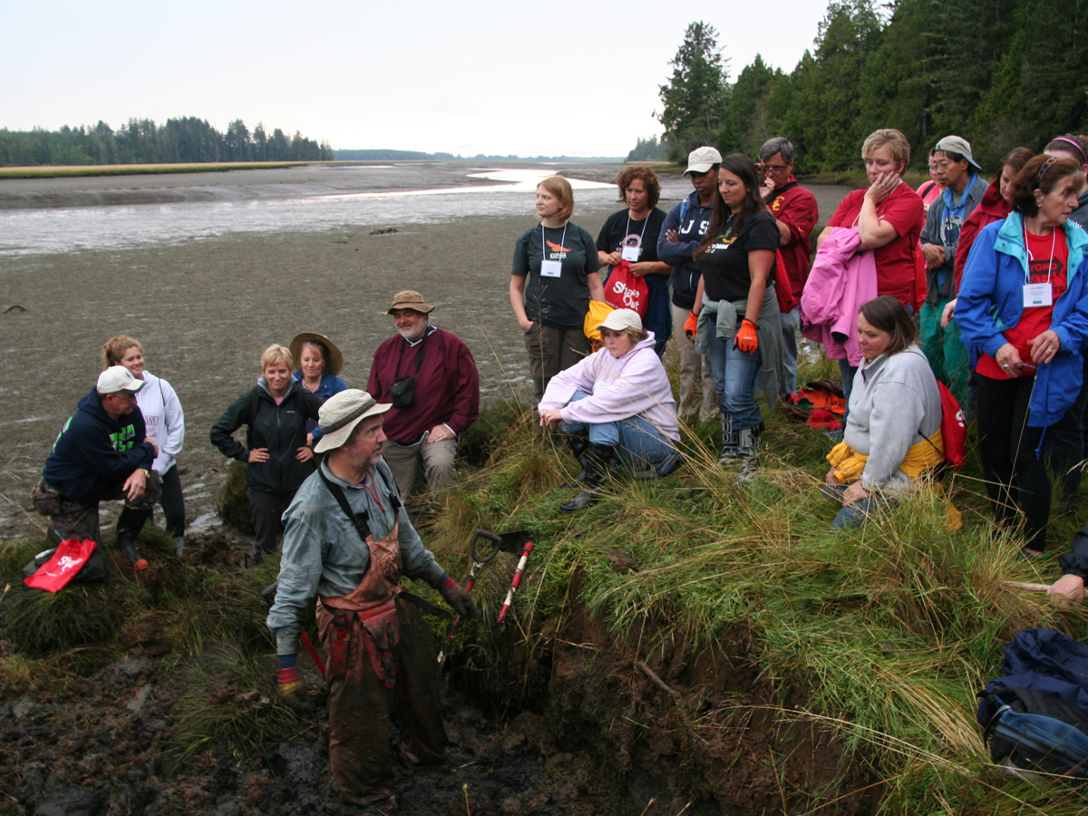 CEETEP participants learn about tsunami geology from US Geological Survey research, Brian Atwater. Niawiakum River, Washington. Participants are gathered at the edge of the salt marsh as Brian explains the layers observed below.