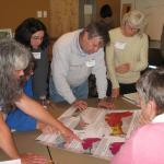 Action team works together on a community hazard inventory activity using maps of relative earthquake hazard (landslides, liquefaction, and amplification) and tsunami inundation.