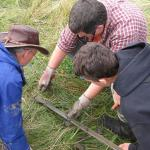 Three CEETEP participants examine a sediment core containing a tsunami sand layer from the banks of the Niawiakum River, WA.