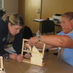 Two workshop participants use a model made of nuts, bolts, and popsicle sticks to simulate buildings in an earthquake. They practice different methods to make the building robust against shaking.